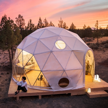 A guest sitting on the deck outside a geodesic dome at sunset.