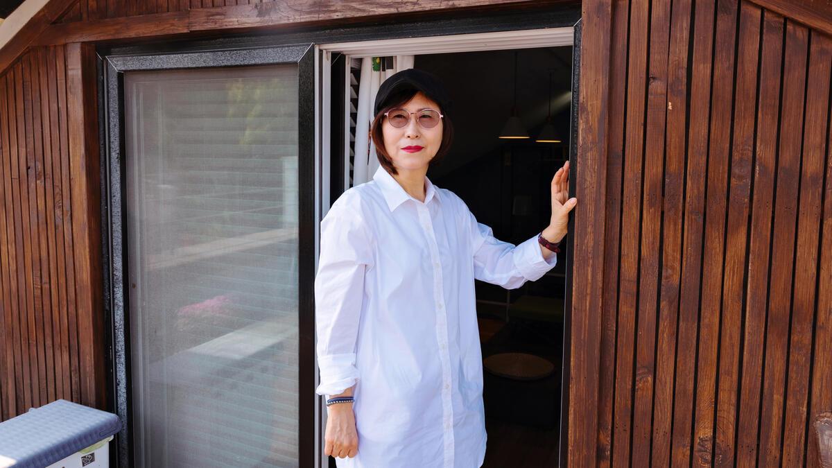 Žena stojí vo dverách v bielej košeli na gombíky a tmavých okuliaroch.