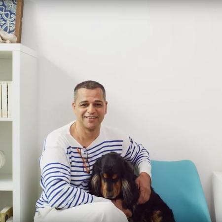 Un hombre está sentado en una silla azul con su perro en el regazo.