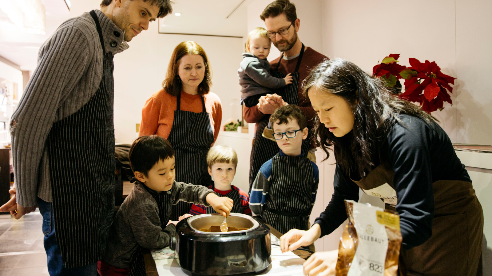 Guests of all ages talking to and cooking with a Host