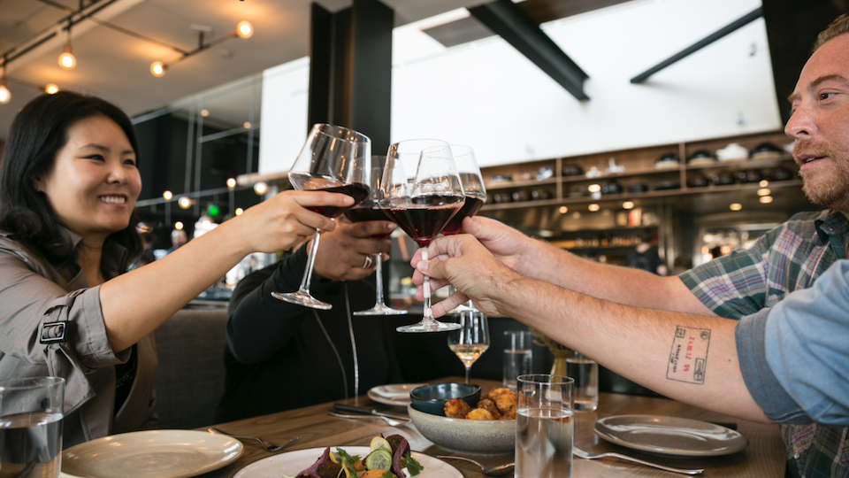 Host and guests toasting with glasses of red wine at a modern local restaurant