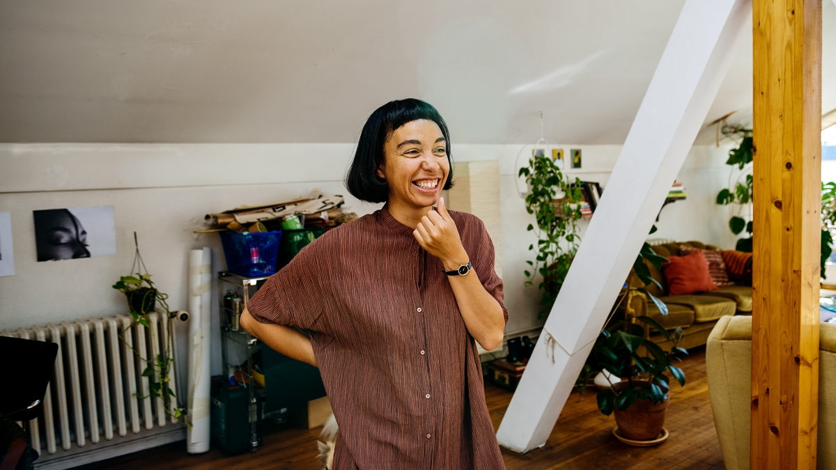 Eine Frau fasst sich ans Kinn und lacht.