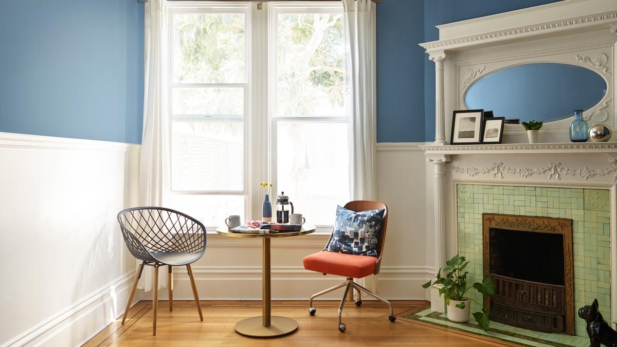 Blaues Wohnzimmer mit Kamin in der Ecke.