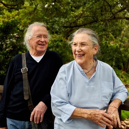Muž a žena stoja vonku a smejú sa.