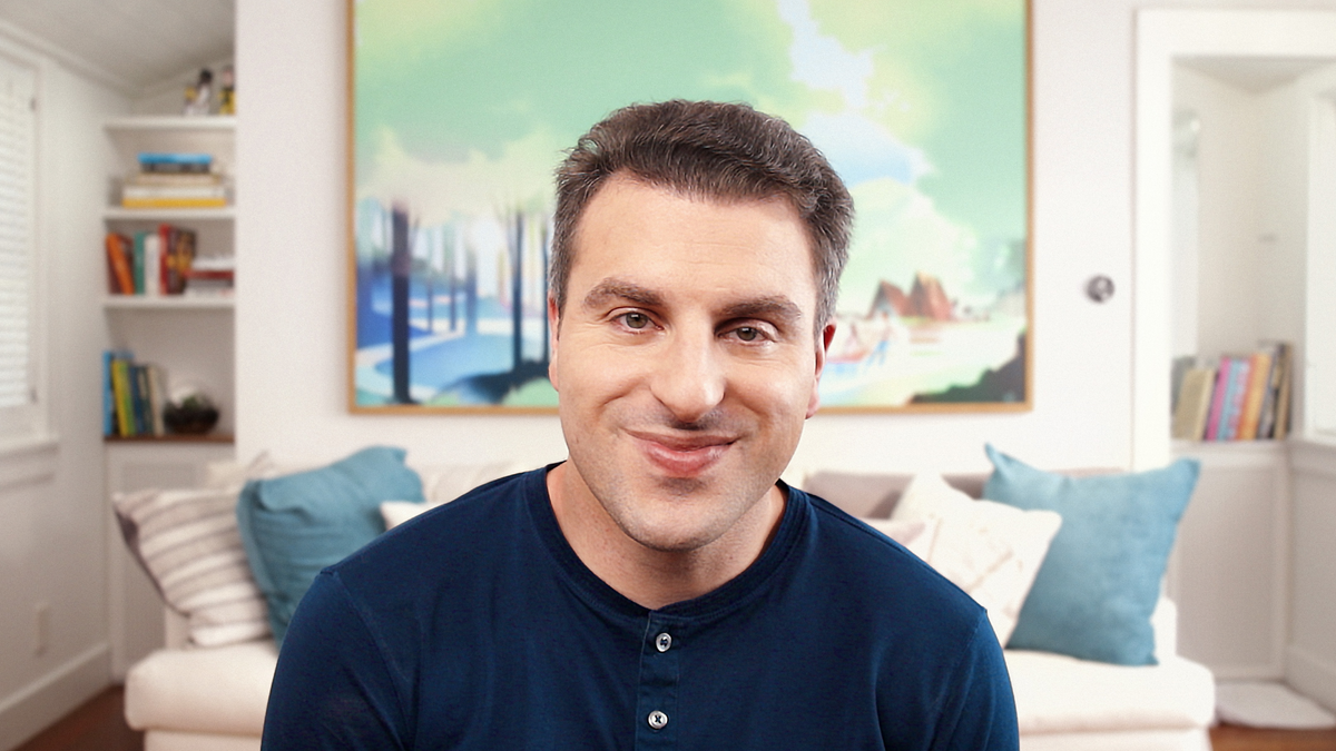 A man in a navy shirt smiles from his home office, which includes a couch under a large painting of a campsite in nature.