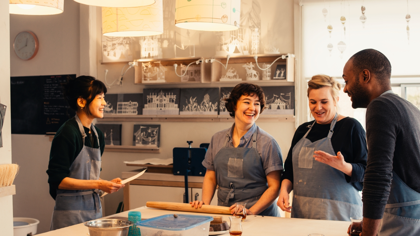 Hosts and Guest laughing in a kitchen around a table.