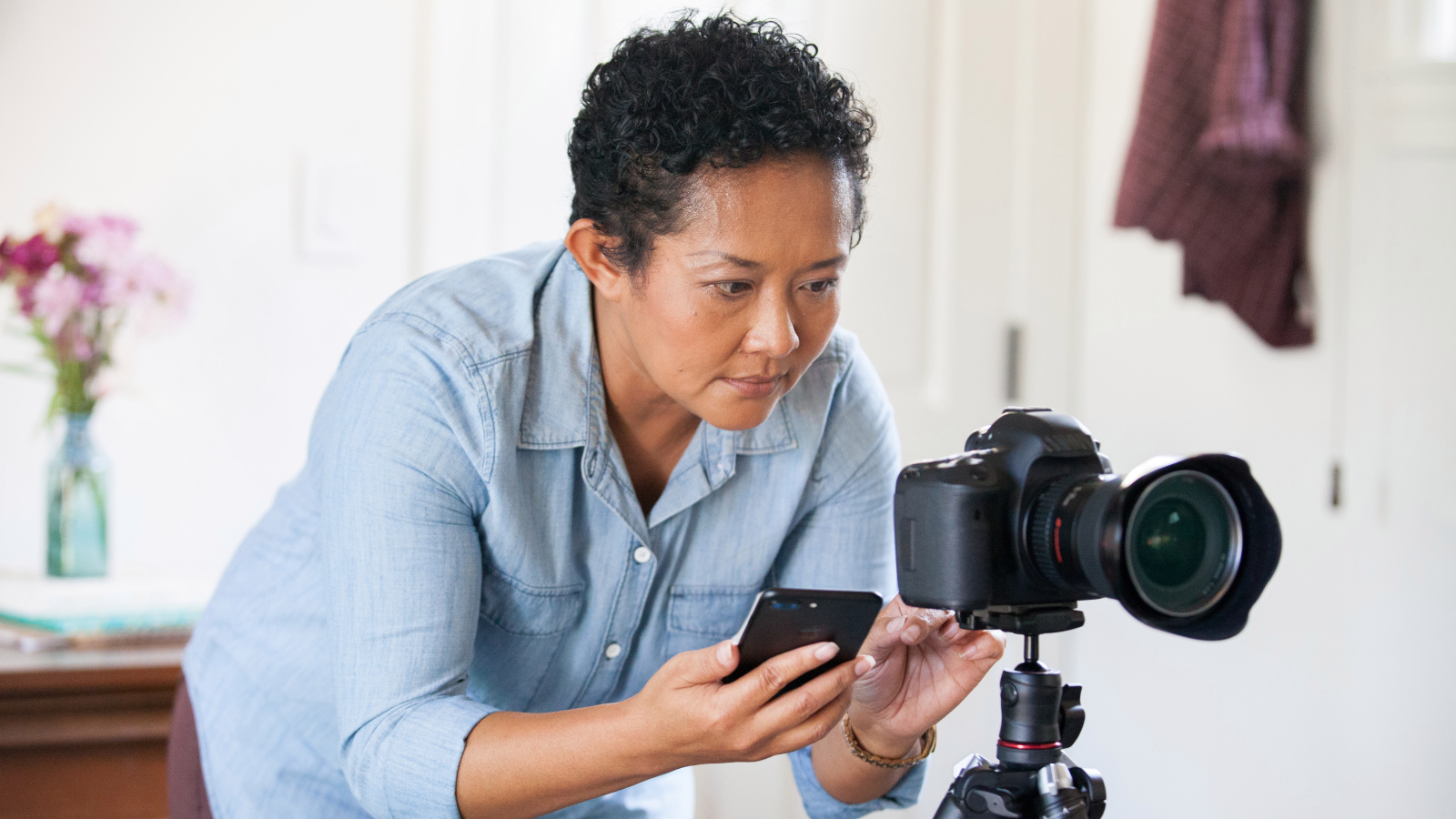 Host with short hair wearing a blue shirt taking a photo with a DSLR camera