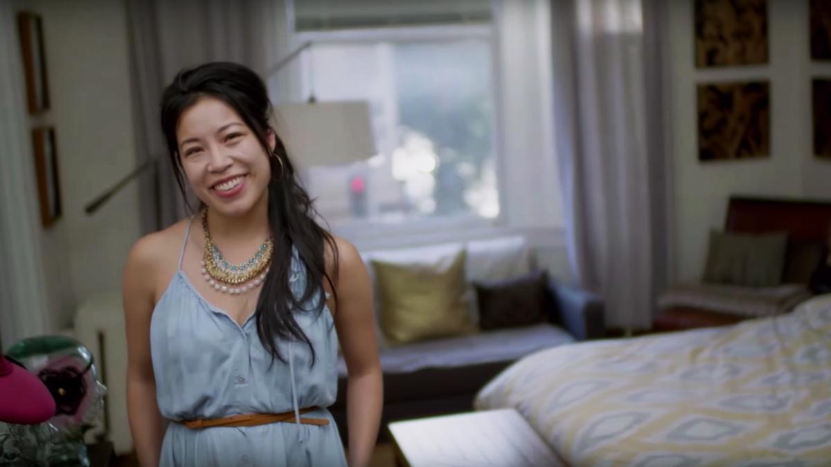 Eine Frau lächelt in ihrem Schlafzimmer.