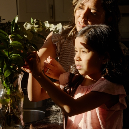 The Host helps her daughter arrange fresh flowers at the kitchen table.