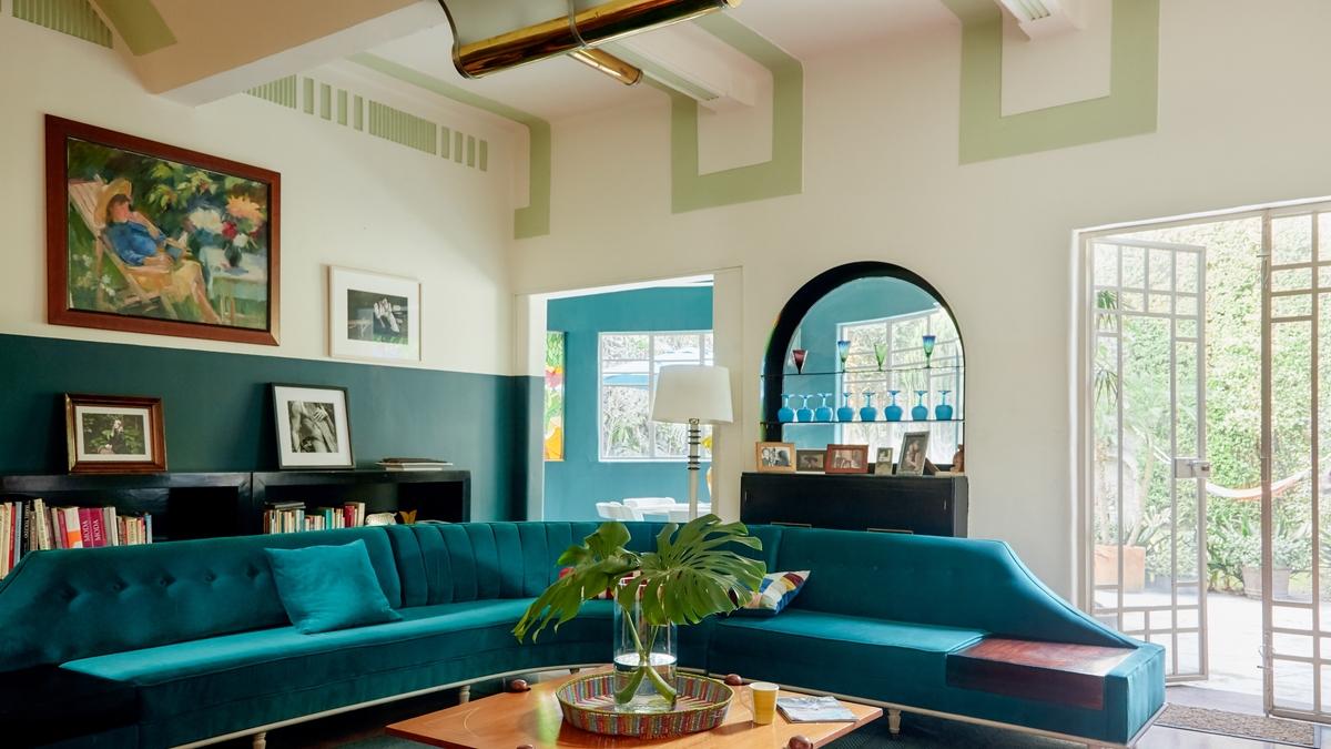 Ein helles und luftiges Wohnzimmer mit einer türkisfarbenen Couch.
