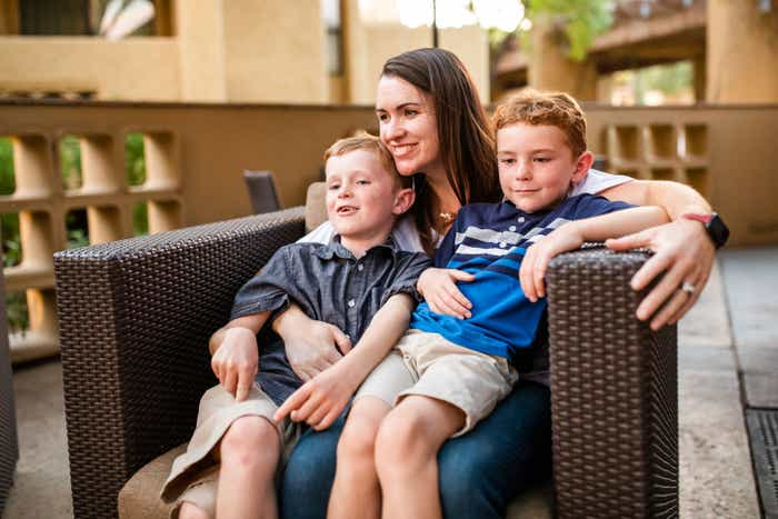 Author Jessica Averett (middle) holds her two sons (left, right) on a chair outside the Scottsdale Resort patio.