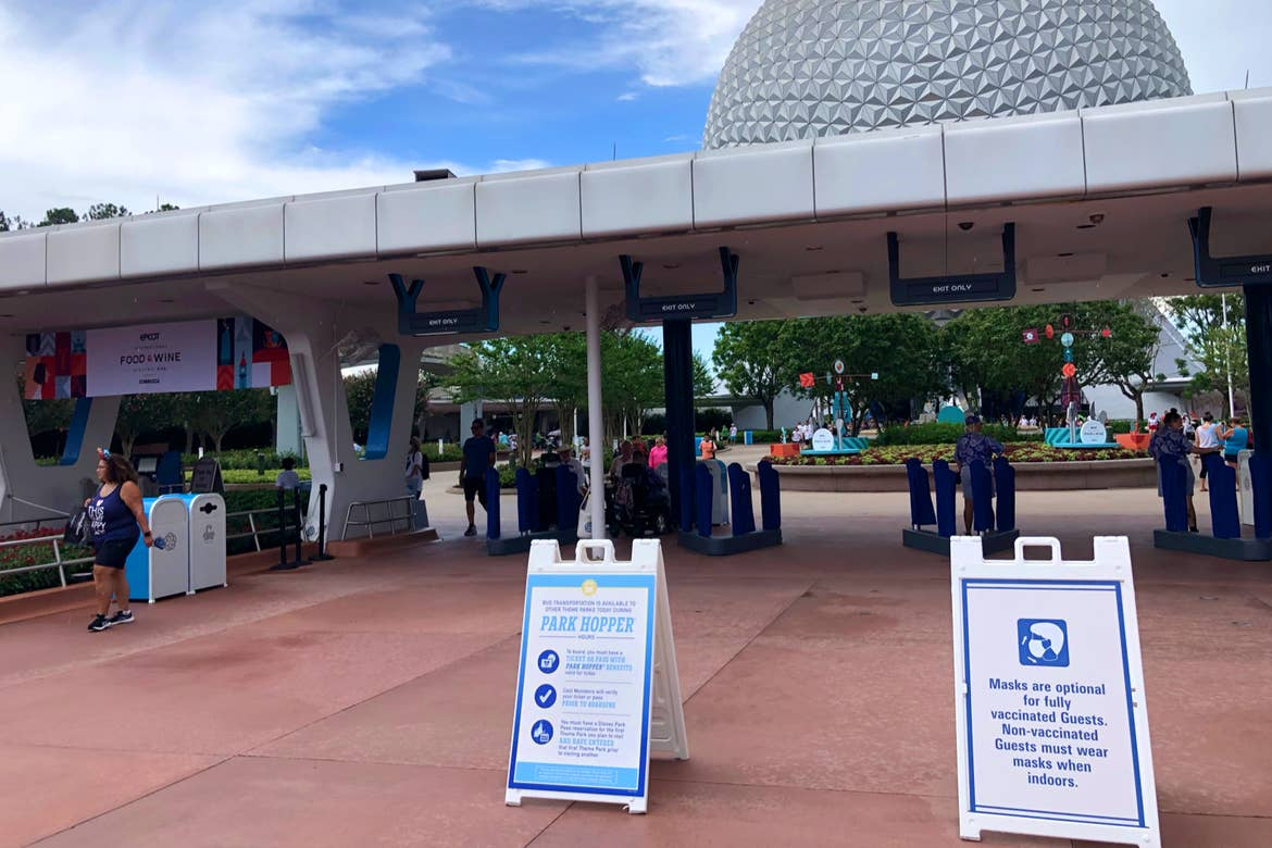 The security entrance to Epcot with two signs indicating CDC safety guidelines for guests conduct in the parks.
