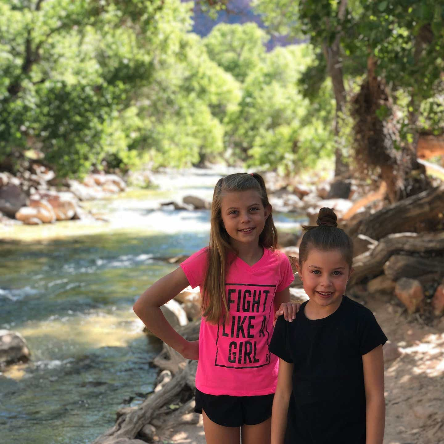 Kyndall (left) and Kyler (right) stand in front of a lush creek in Zion.