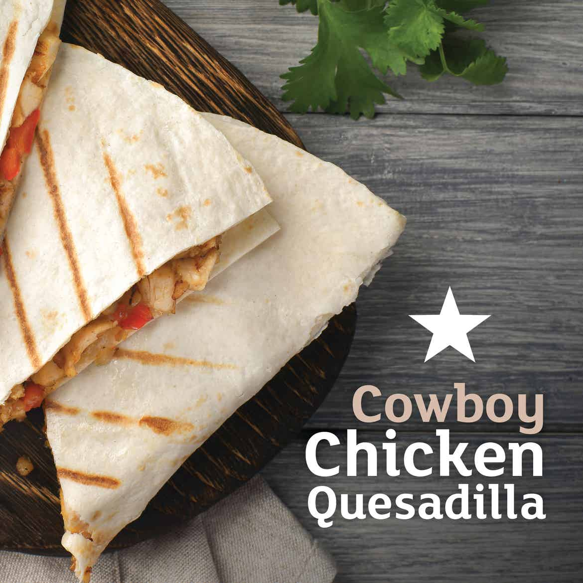 Three wedges of a quesadilla on a wooden cutting board and grey plank table. Type on the left says, 'Cowboy Chicken Quesadilla.'