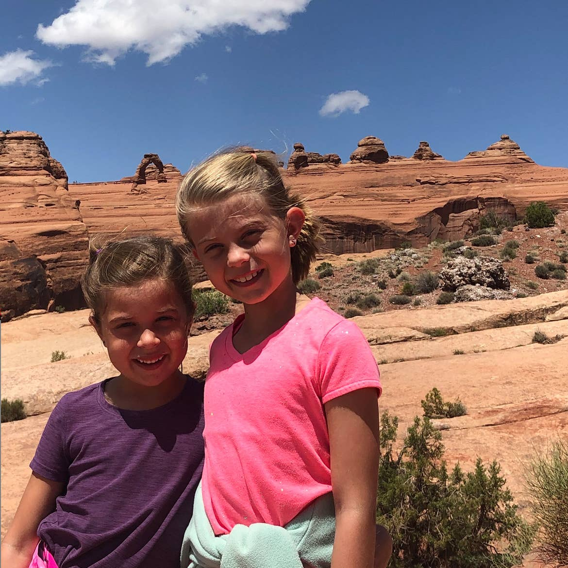 Kyndall and Kyler stand in front of the mountains of Red Rocks.