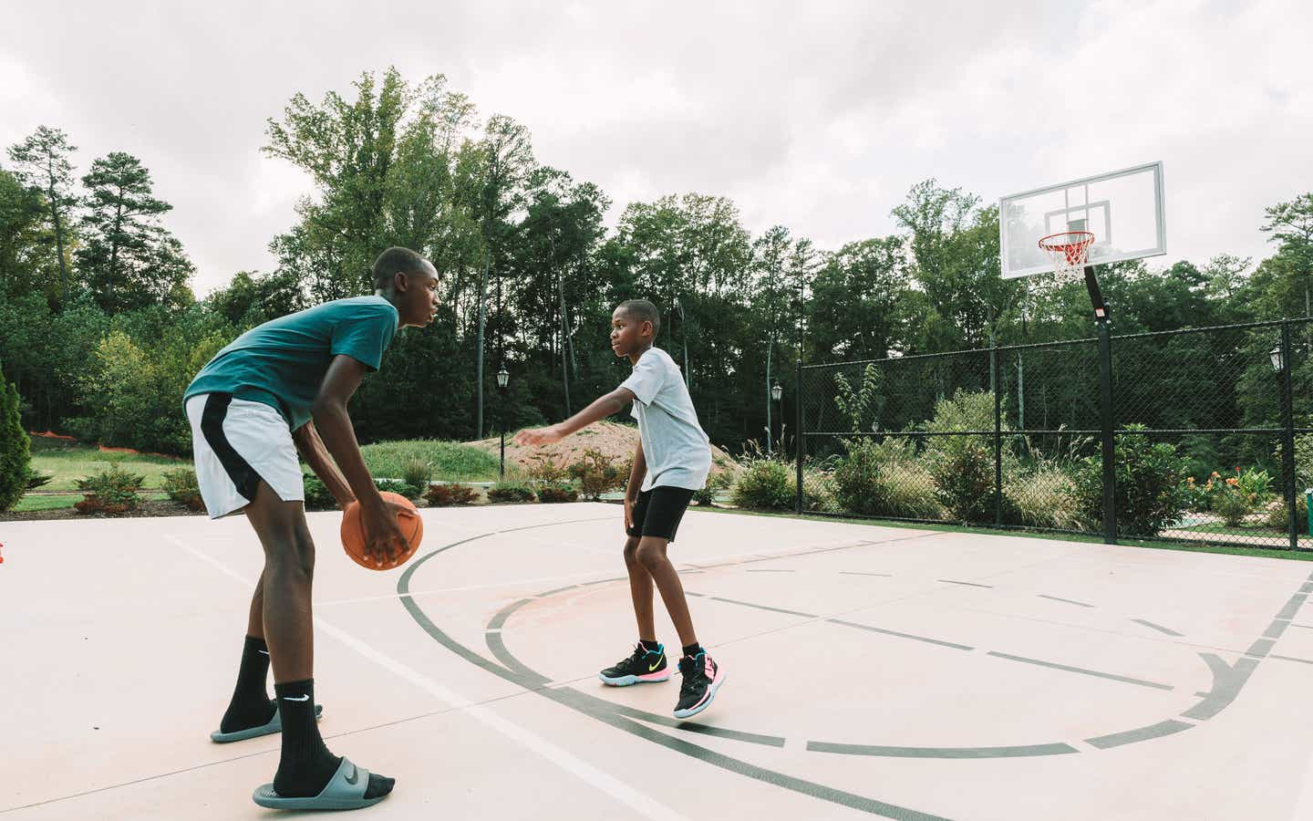 Adult and child playing basketball outdoors at Williamsburg Resort.