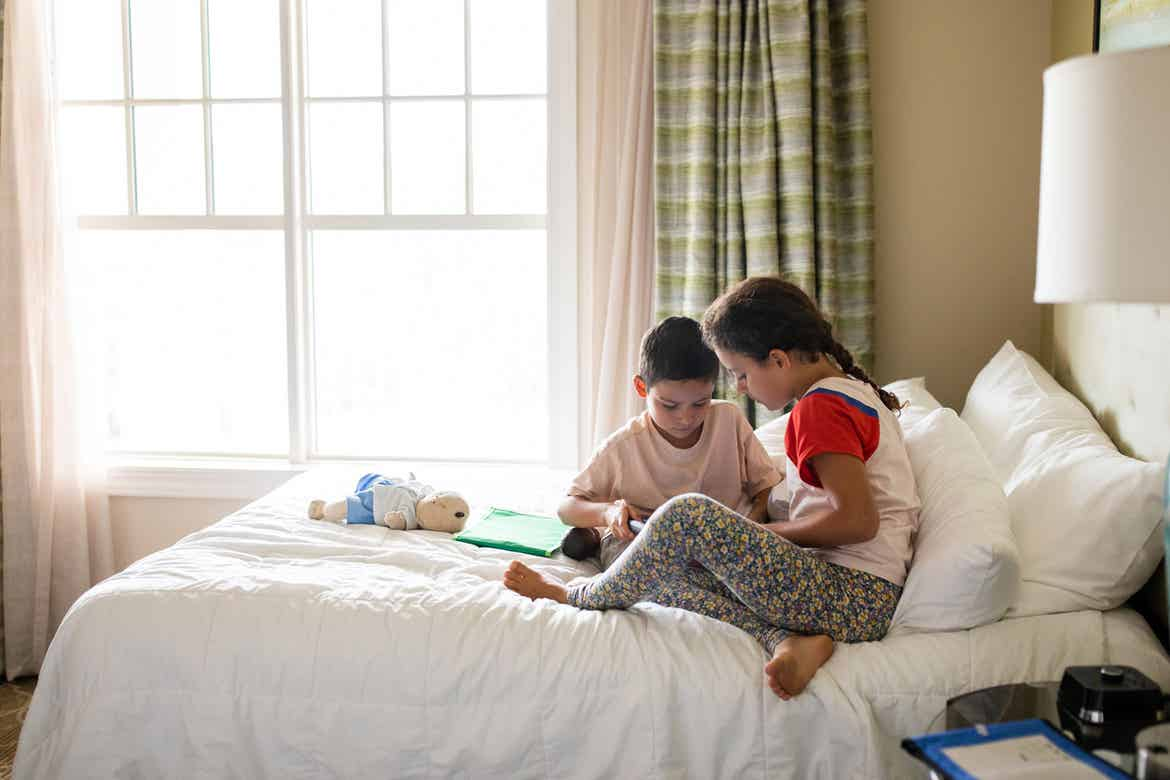 Brenda Rivera Sterns' two children sit in one of the bedrooms on a queen-sized bed in our Signature Collection villa at our South Beach Resort in Myrtle Beach, South Carolina.