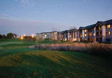 Outdoor golf course at sunset with view of property buildings in the background at Lake Geneva Resort
