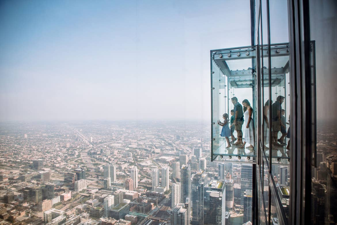 A woman, man, a young boy and young girl stand in a protruding glass box at the Willis Tower SkyDeck.