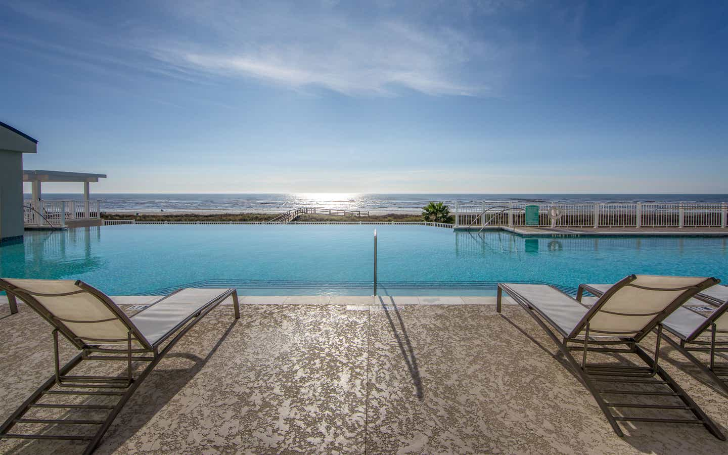 Outdoor oceanfront pool with sun chairs at Galveston Seaside Resort.