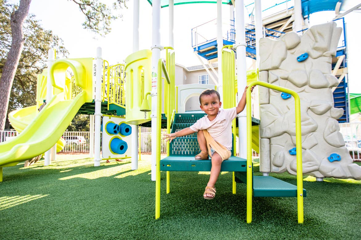 Author, Brenda Rivera Stearns' son climbs the green steps of our playground at our South Beach resort in Myrtle Beach, South Carolina.
