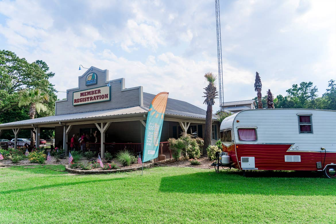 A wooden-sided building with a marquee that reads, 'Member Registration' stands under a cloudy blue sky near a white and red travel camper trailer at the Villages resort.