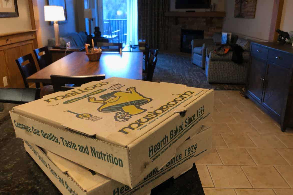 Two pizza boxes placed on a black countertop in a villa.