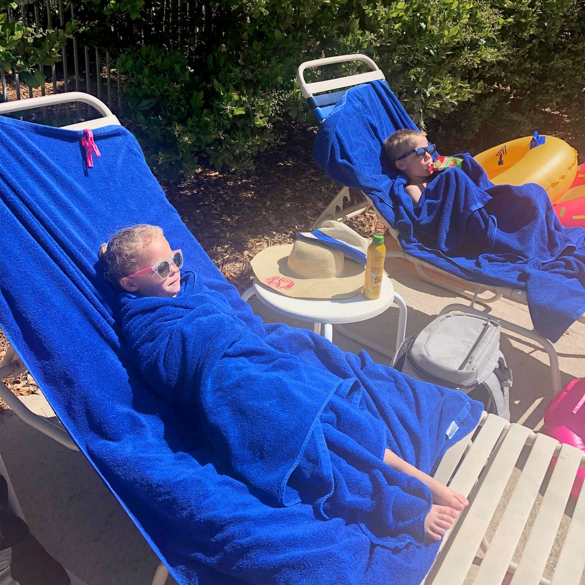 Featured Contributor, Brianna Steele's children sit wrapped in blue towels after a dip in the pool.