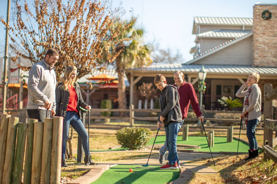 The Nall family gathers around the hole for a mini-golf game.