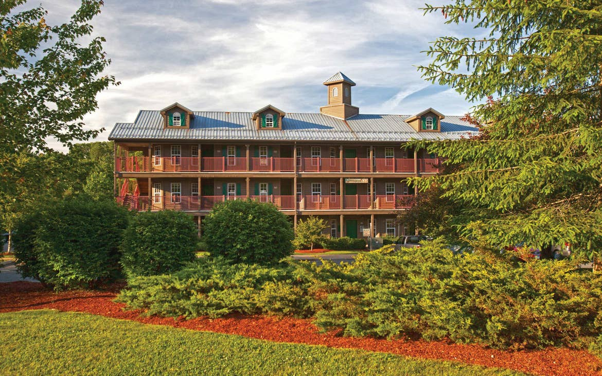 A beautiful shot of an Oak n' Spruce Resort building with lush greenery in the foreground