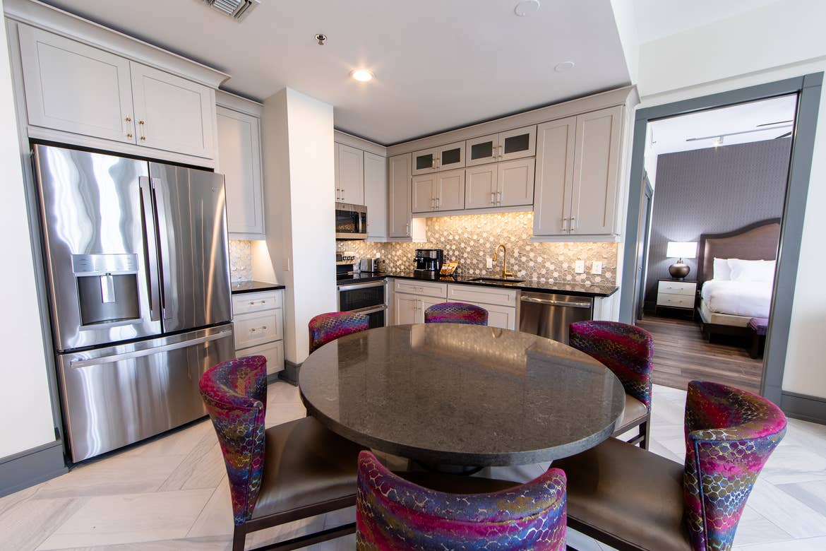 Signature Collection two-bedroom villa dining area table, five chairs and full kitchen at New Orleans Resort in Louisiana.