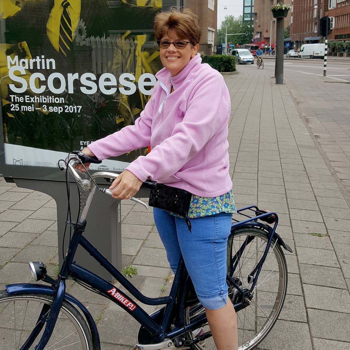 A caucasian woman wearing a pink fleece sweater and jeans sits atop a bicycle on the streets of Amsterdam.