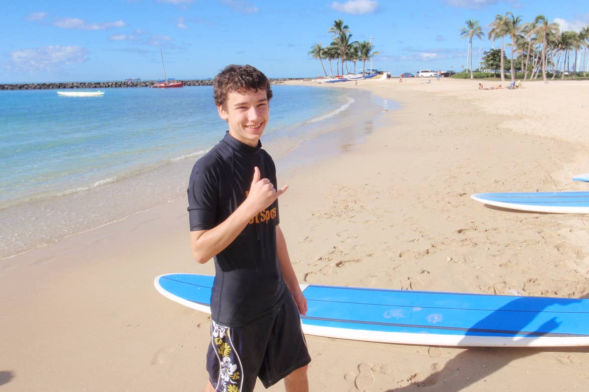 A caucasian male gestures 'hang ten' with his right hand while wearing a wetsuit near two blue surfboards on a beach.
