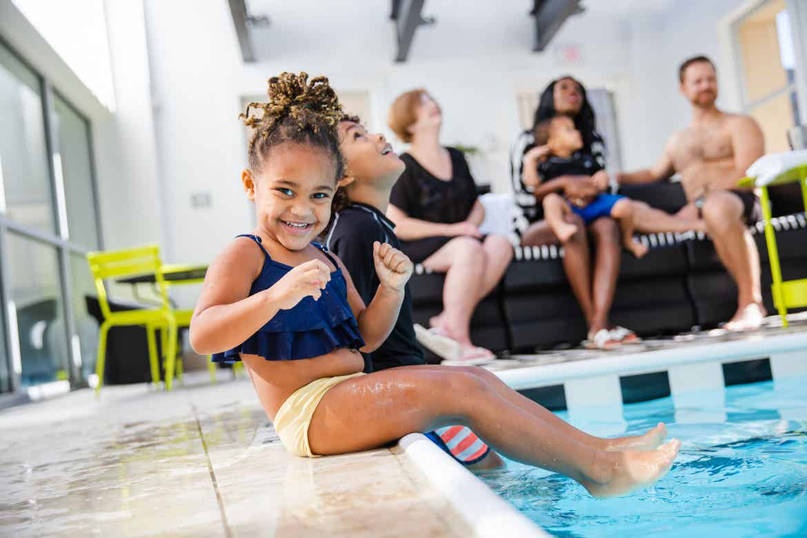 Featured author, Sally Butan of @butanclan, children dip their feet into the pool as her daughter looks at the camera wearing a swimsuit.