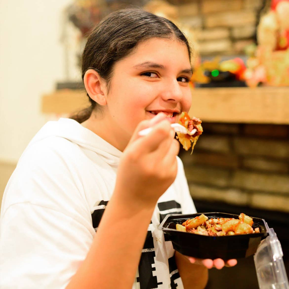 A young girl eats some loaded buffalo chicken mac & cheese indoors.