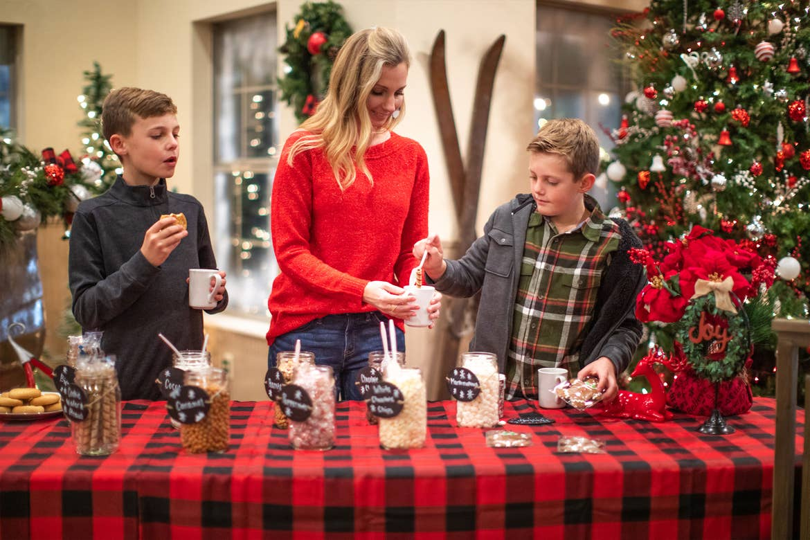 Author, Amanda Nall (middle), preps some hot cocoa with her sons as they pick different toppings.