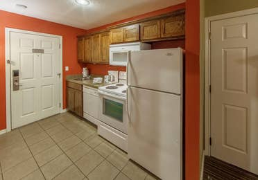 Kitchen with fridge, microwave, oven, dishwasher, and sink in a studio room at Piney Shores Resort in Conroe, Texas