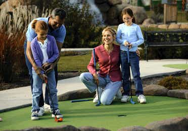 Family of four playing mini golf