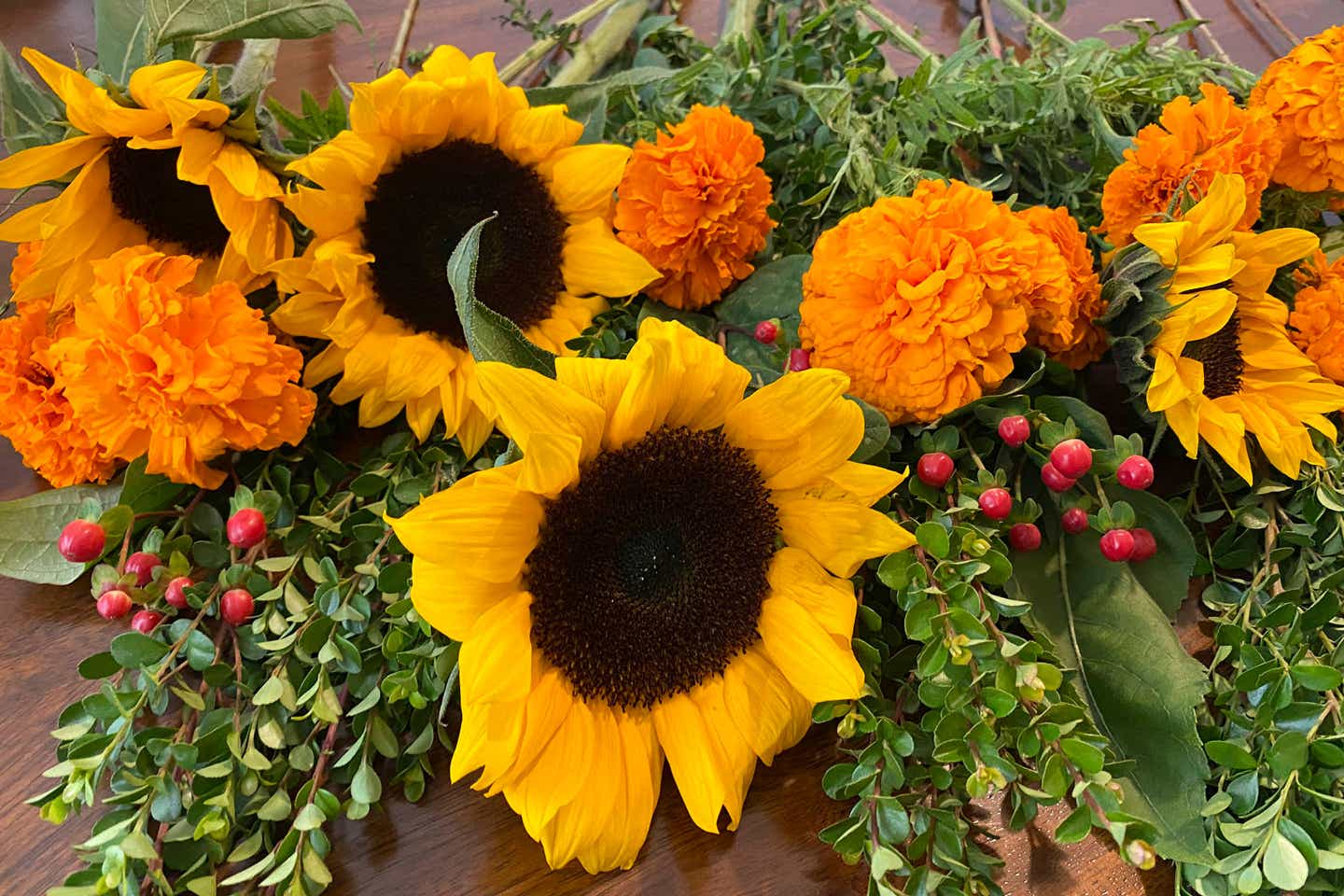 Seasonal floral arrangement featuring sunflowers, marigolds and holly branches are spread across a kitchen table top.