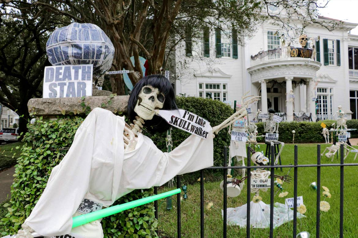 A group of fake skeletons placed in a front yard.