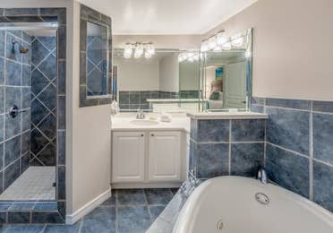 Bathroom with whirlpool tub, walk-in shower, and sink with large mirror in a two-bedroom villa at Panama City Beach Resort