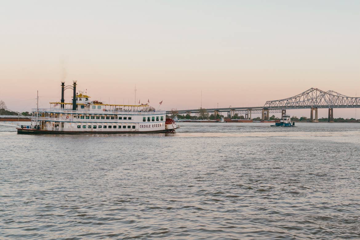 A riverboat named the 'Creole Queen' floats along the Mississippi River in front of the Crescent City Connection bridge under a sunset sky.