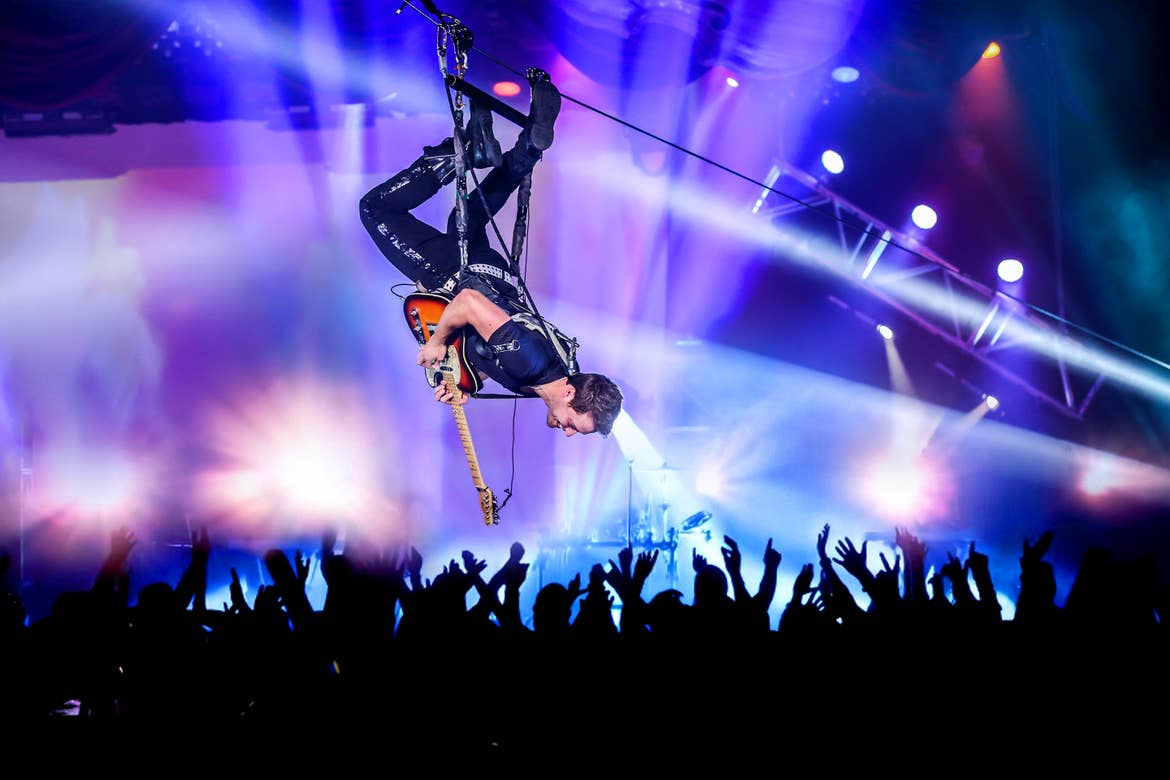 A guitarist wears a harness as he hangs upside down over a crowd of people in a theater.