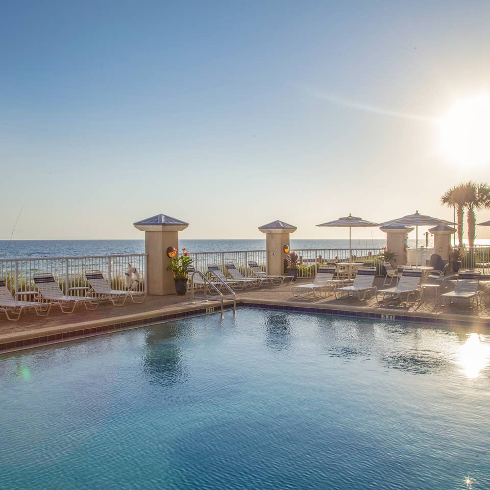 Outdoor pool with beach chairs surrounded by palm trees at Panama City Beach Resort