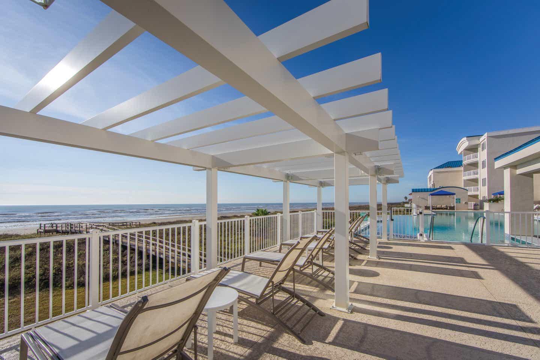 Beach chairs near a pool sitting under a pergola at Galveston Seaside Resort