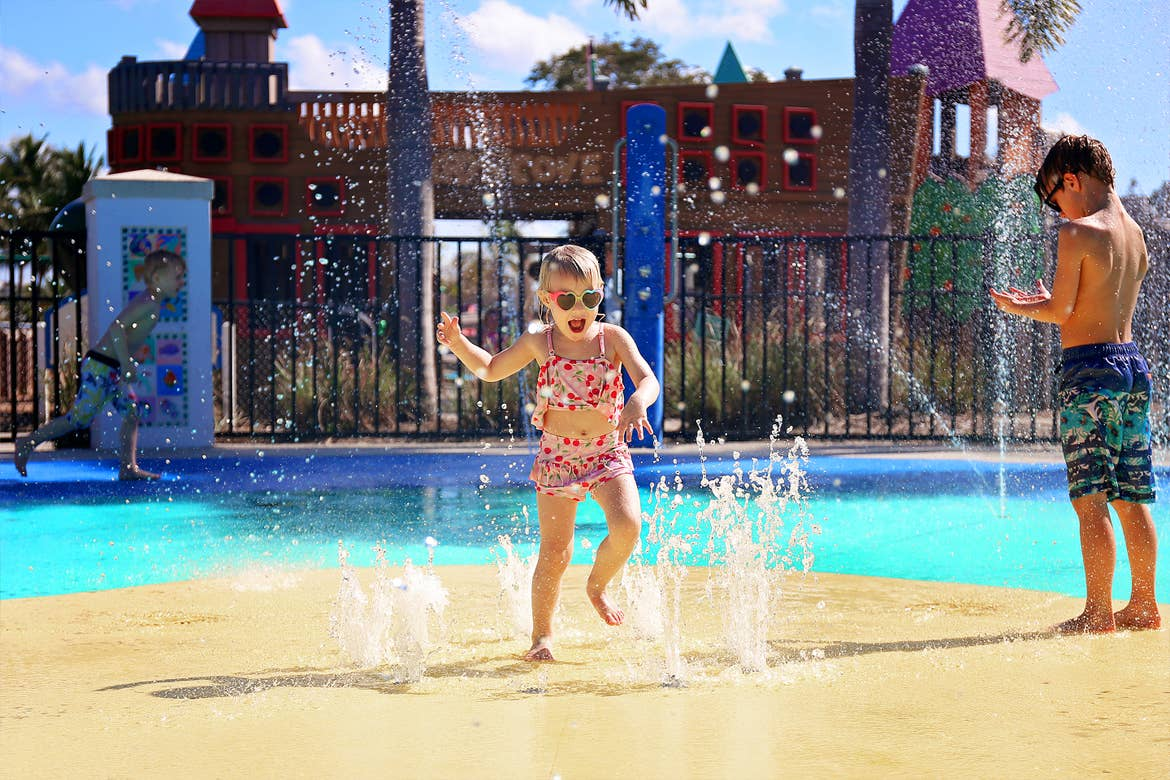 A caucasian girl (left) wears a swimsuit and sunglasses near a caucasian boy (right) wearing swim trunks as they play in a splash pad outdoors.