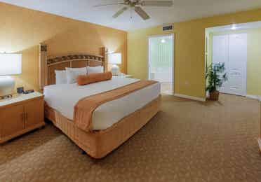 Master bedroom with king bed and attached bathroom in a two-bedroom villa at Cape Canaveral Beach Resort