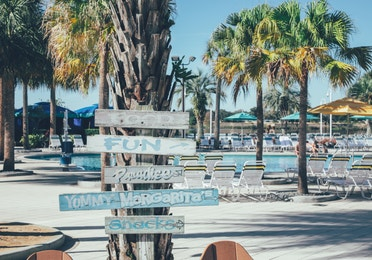 Property signage with pool and palm trees in background in the West Village at Orange Lake Resort near Orlando, Florida