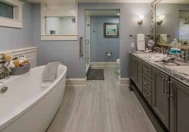 A bathroom with a spa-like bathtub in a four-bedroom Signature Collection villa at Cape Canaveral Resort