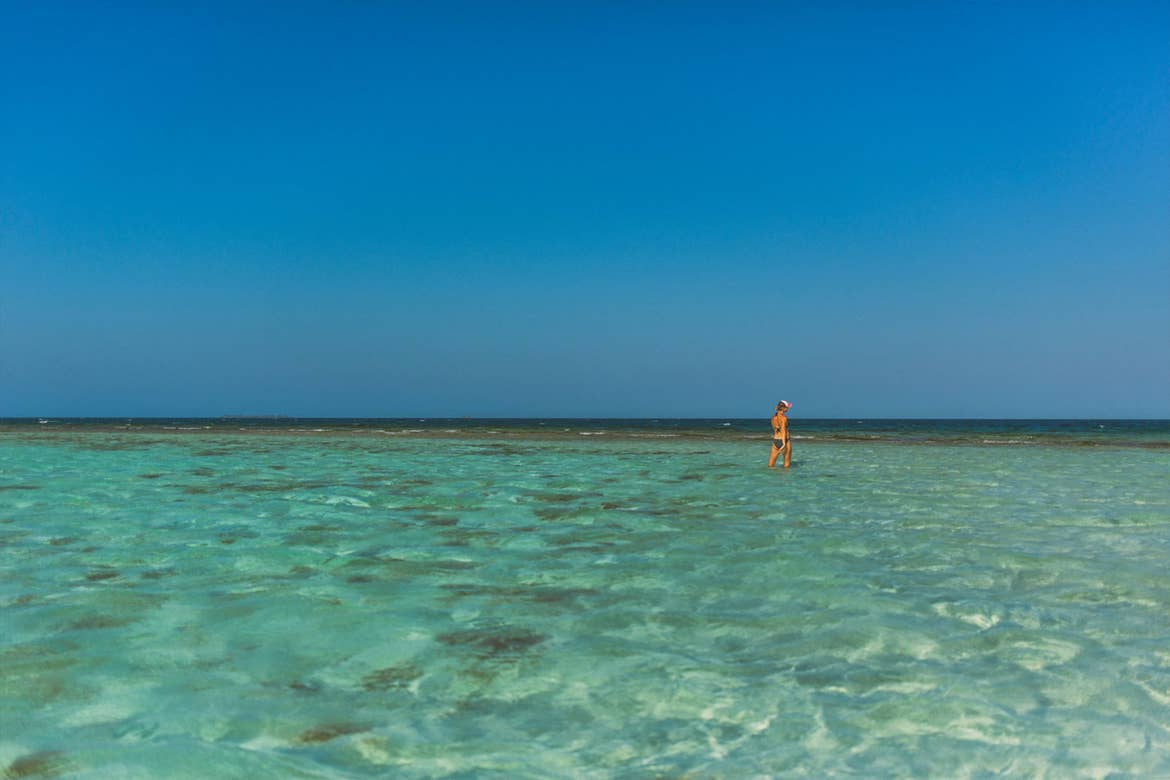 A woman stands out in the crystal blue ocean water.